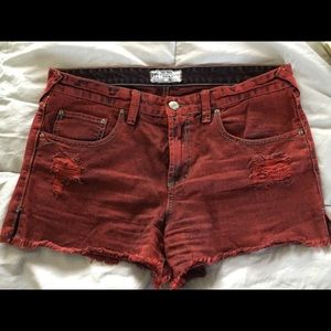 Free people red brick colored distressed shorts.
